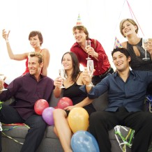 Group of Young People at a Party Sitting on a Couch with Champagne