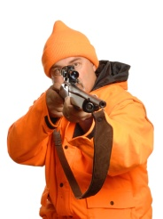 hunter pointing rifle in blaze orange gear